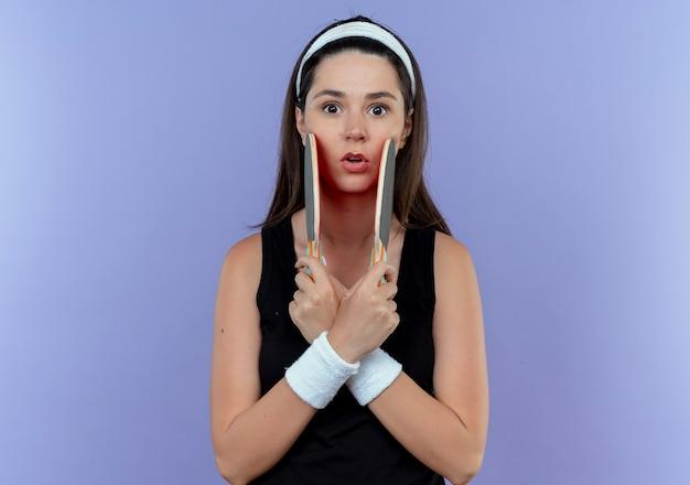 Jeune femme de remise en forme en bandeau tenant des raquettes pour table de tennis regardant la caméra surpris en traversant les mains debout sur fond bleu
