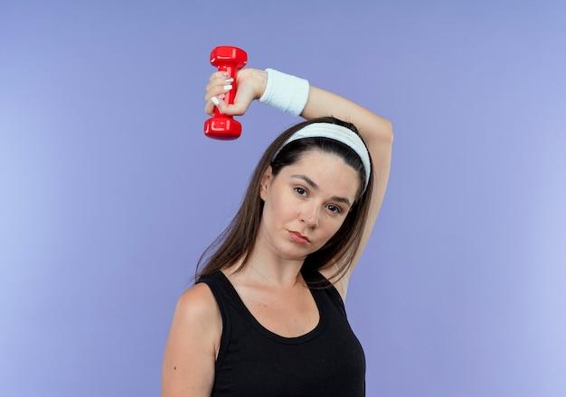 Jeune femme de remise en forme en bandeau travaillant avec haltère à la recherche de tension et confiant debout sur fond bleu