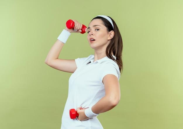 Jeune femme de remise en forme en bandeau travaillant avec des haltères à la confiance debout sur un mur léger