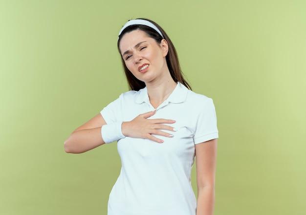 Jeune femme de remise en forme dans le bandeau à la recherche de mal tenant la main sur sa poitrine se sentant mal à l'aise debout sur un mur léger