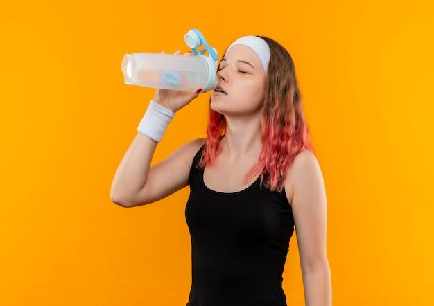 Jeune femme de remise en forme dans l'eau potable de sportswear avec les yeux fermés debout sur le mur orange