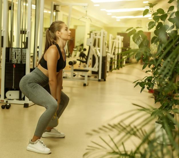 Jeune femme de remise en forme faisant des exercices de squats avec kettlebell dans la salle de gym. entraînement fonctionnel avec poids libres