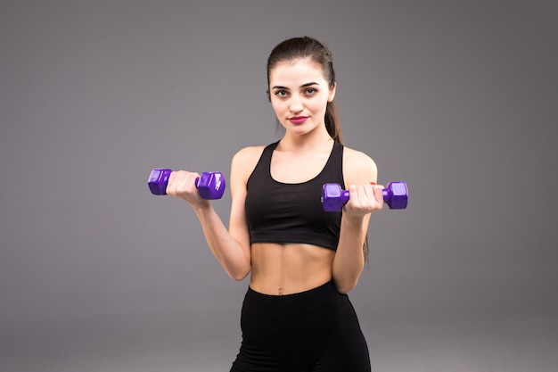 Jeune femme de remise en forme avec des haltères sur un mur gris. style de vie sportif.