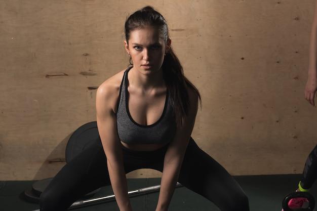 Jeune femme de remise en forme de levage poids lourd bouilloire bell au gymnase