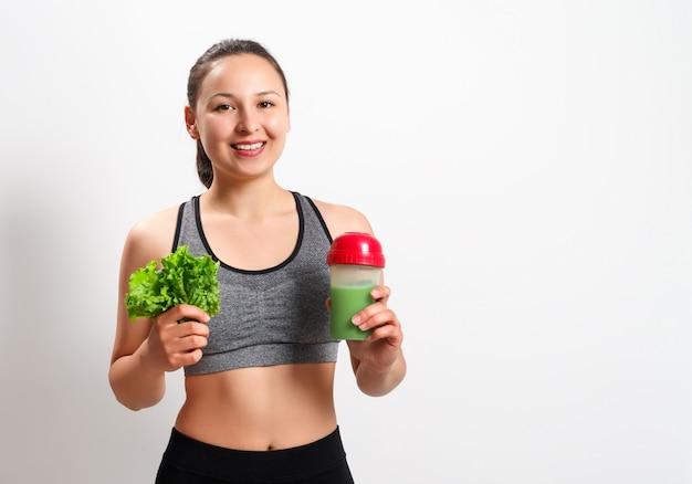 Jeune femme de remise en forme avec salade et cocktail diététique sur un blanc