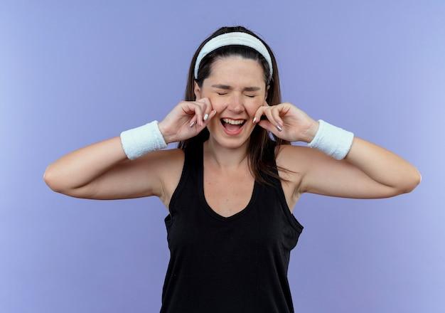 Jeune femme de remise en forme en serre-tête fermant les oreilles heureux et excité debout sur le mur bleu