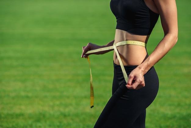 Jeune femme de remise en forme en sportswear noir avec une taille parfaite avec un ruban à mesurer dans les mains