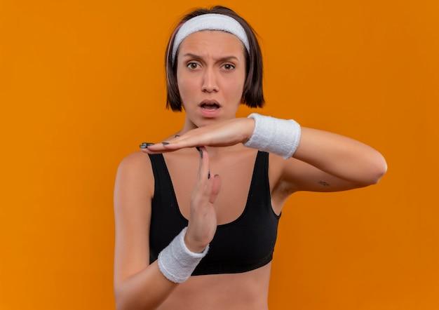 Jeune femme de remise en forme en tenue de sport avec bandeau faisant le geste de temps à la confusion debout sur le mur orange