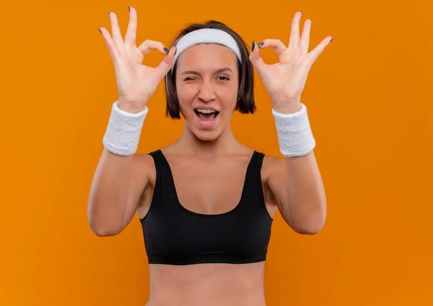 Jeune femme de remise en forme en tenue de sport avec bandeau souriant et clignotant faisant signe ok avec les deux mains debout sur un mur orange