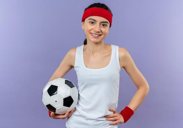 Jeune femme de remise en forme en tenue de sport avec bandeau tenant un ballon de football souriant confiant heureux et positif debout sur mur violet