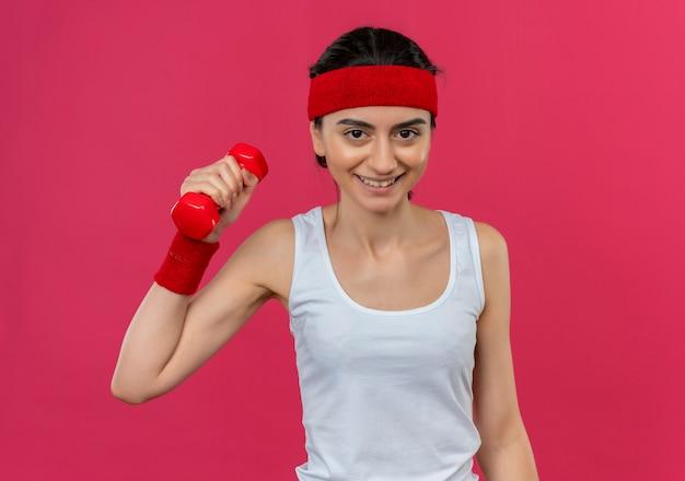 Jeune femme de remise en forme en tenue de sport avec bandeau tenant haltère en main levée souriant confiant faisant des exercices debout sur un mur rose