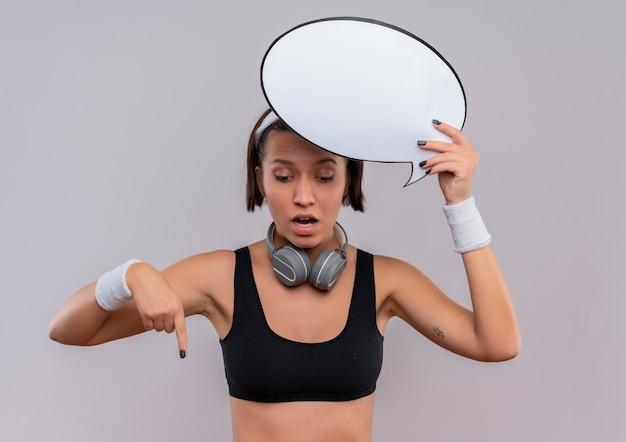 Jeune femme de remise en forme en tenue de sport avec bandeau tenant le signe de bulle de discours vide pointant le doigt wi vers le bas à surpris debout sur un mur blanc