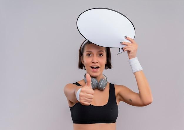 Jeune femme de remise en forme en tenue de sport avec bandeau tenant signe de bulle de discours vide souriant joyeusement montrant les pouces vers le haut debout sur un mur blanc