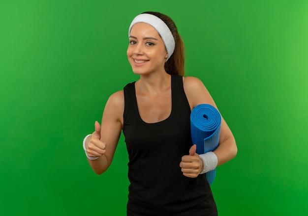 Jeune femme de remise en forme en tenue de sport avec bandeau tenant un tapis de yoga montrant les pouces vers le haut souriant confiant debout sur mur vert