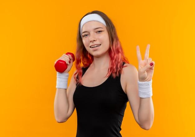 Jeune femme de remise en forme en tenue de sport tenant haltère souriant joyeusement montrant signe de la victoire debout sur un mur orange