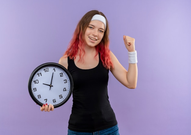 Jeune femme de remise en forme en tenue de sport tenant une horloge murale serrant le poing heureux et sorti debout sur un mur violet