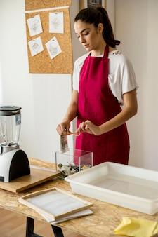 Jeune femme remplissant un récipient en verre avec des morceaux de papier