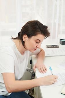 Jeune femme remplissant et signant le formulaire à une table
