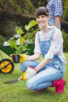 Jeune femme, rempotage, a, plante, dans jardin