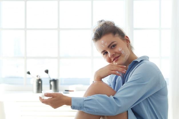 Jeune femme répandant la crème pour le visage. concept de soins de la peau.