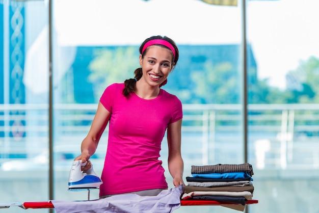 Jeune femme repassant des vêtements à bord