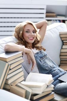 Jeune femme reposant sur le canapé avec beaucoup de livres