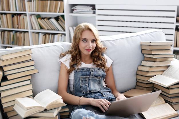 Jeune femme reposant sur le canapé avec ordinateur portable et beaucoup de livres