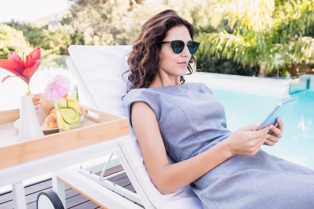 Jeune femme reposante sur une chaise longue à l'aide d'une tablette numérique près de la piscine