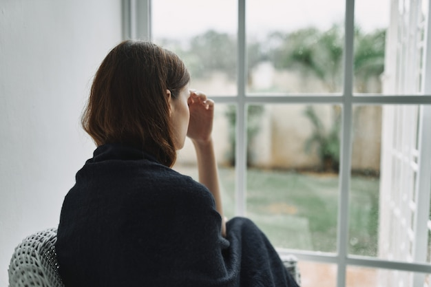 Jeune, femme, reposer, fauteuil, maison, fenêtre