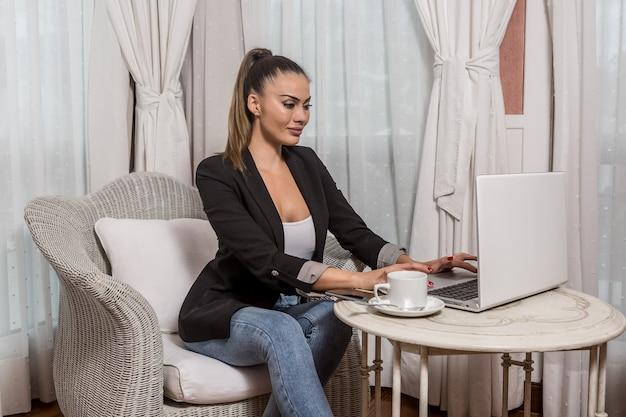 Jeune femme en réseau dans une chambre d'hôtel