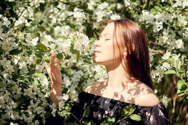 Une jeune femme respire l'odeur d'un pommier en fleurs