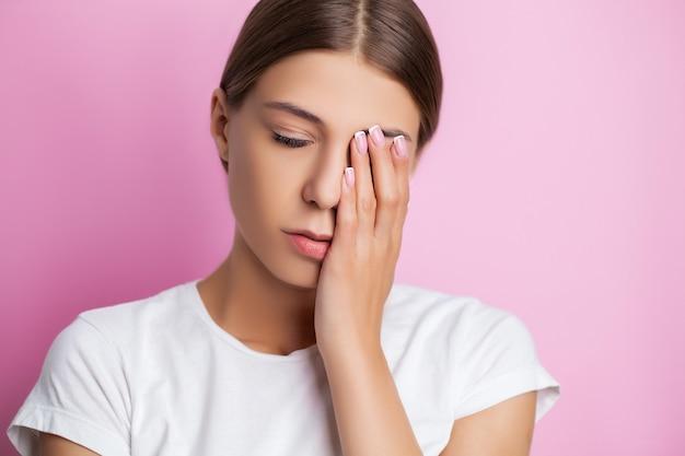 Une jeune femme ressent une douleur intense sur son visage touchant la zone douloureuse avec sa main.