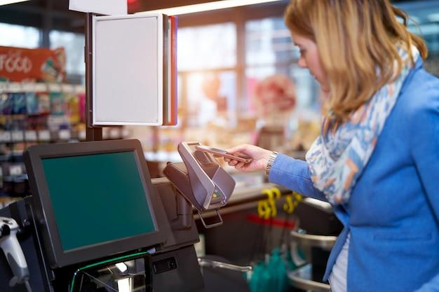 Jeune femme restant devant la machine à payer soi-même