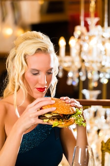 Jeune femme restaurant raffiné manger un hamburger, elle se comporte mal