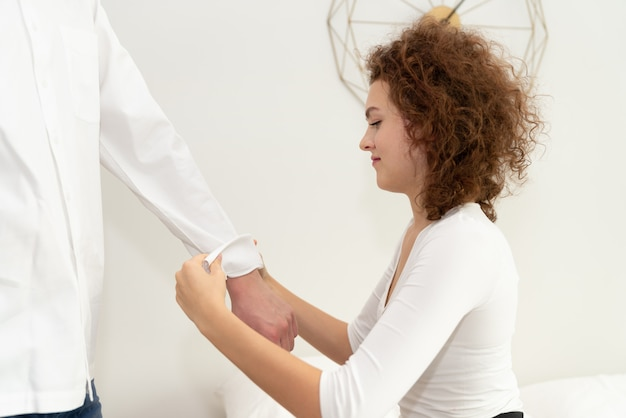 Jeune femme retroussant les manches de son petit ami