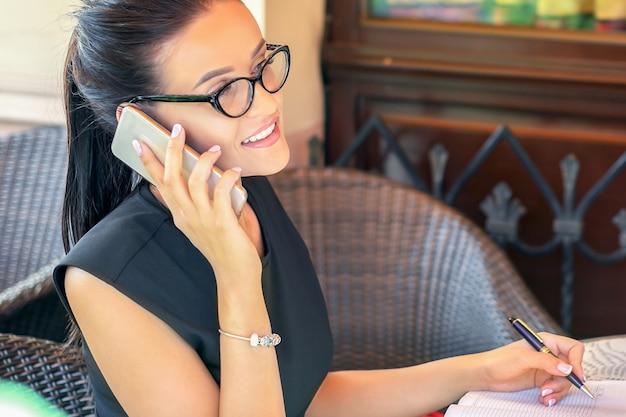 Jeune femme réussie parle par téléphone assis dans un café.