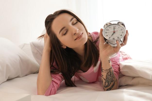Jeune femme avec réveil au lit. tôt le matin