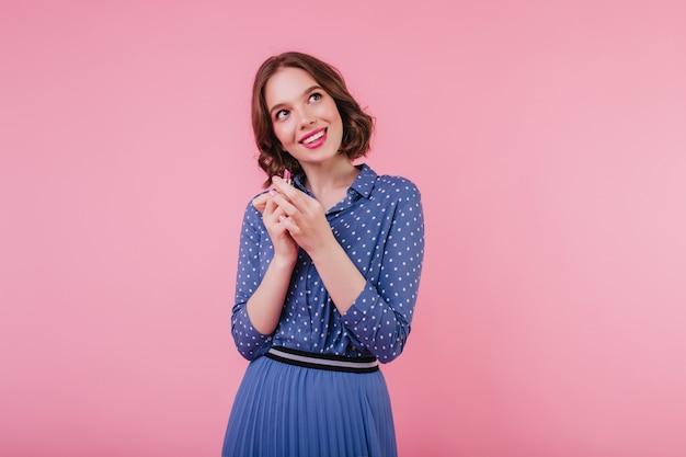 Jeune femme rêveuse aux cheveux noirs posant avec du rouge à lèvres. fille caucasienne en vêtements bleus, faire du maquillage avec le sourire.