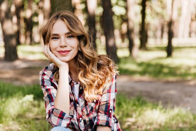 Jeune femme rêveuse en chemise décontractée assise dans le parc et à la recherche. femme romantique aux cheveux ondulés refroidissant dans la chaude journée d'été.