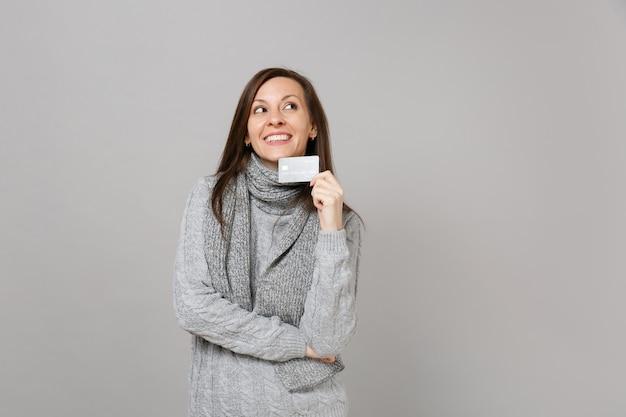 Jeune femme rêveuse en écharpe chandail gris en levant, tenant une carte bancaire de crédit isolée sur fond gris. gens de mode de vie sain émotions sincères, concept de saison froide. maquette de l'espace de copie.