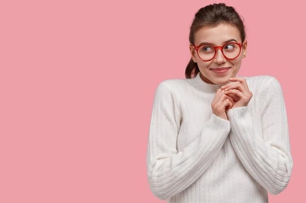 Une jeune femme rêveuse optimiste garde les mains jointes, se concentre sur le côté avec un doux sourire, a l'intention ou planifie quelque chose de grandiose