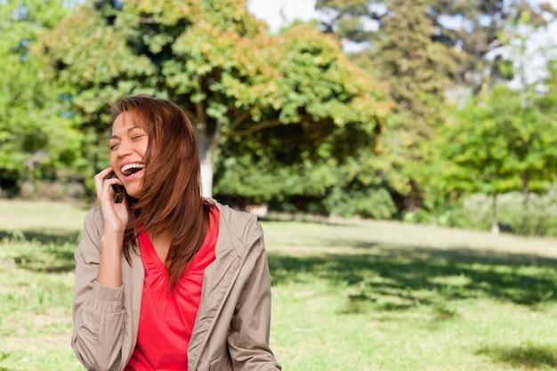 Jeune femme riant avec enthousiasme au téléphone dans une zone de prairie ouverte