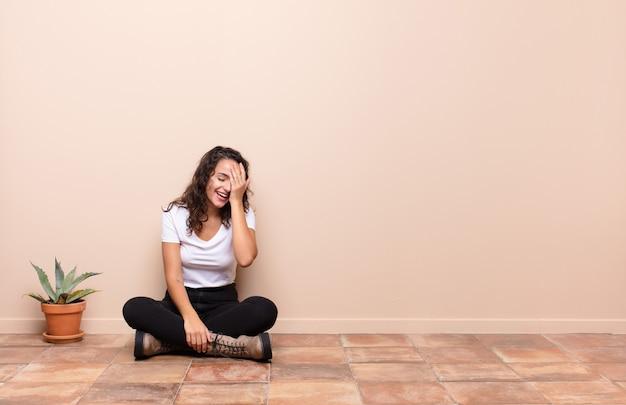 Jeune femme riant et giflant le front comme dire oh! j'ai oublié ou c'était une erreur stupide assis sur le sol d'une terrasse