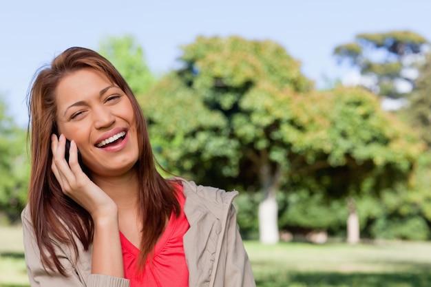 Jeune femme riant joyeusement au téléphone dans un parc lumineux