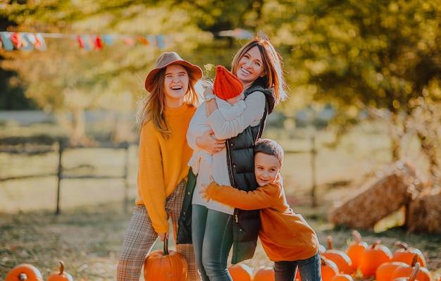 Jeune femme riant avec ses trois enfants mignons au champ de citrouilles. fond d'automne.