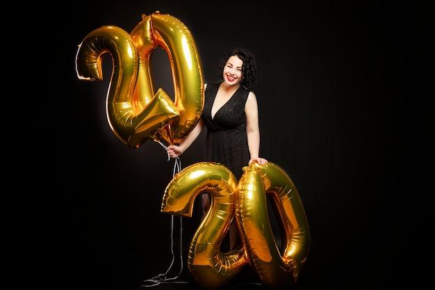 Jeune femme riante avec des boules d'or sous la forme de nombres du nouvel an. brune aux cheveux bouclés avec rouge à lèvres.