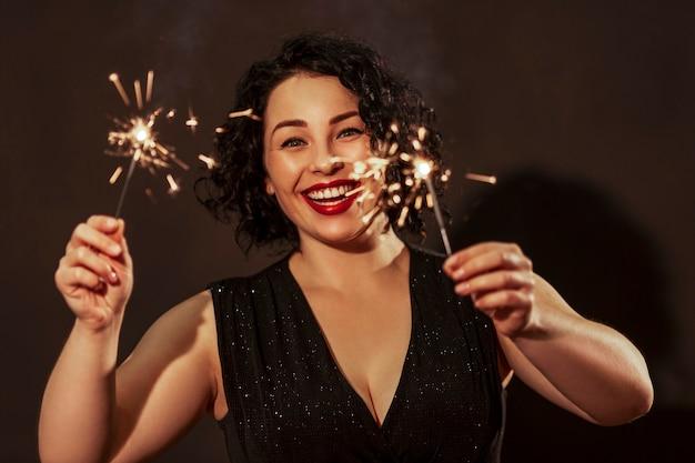 Jeune femme riante avec des cierges magiques. belle brune aux lèvres rouges et aux cheveux bouclés dans une robe de fête. fêtes et événements. nouvel an et noël.