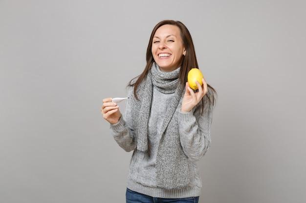 Jeune femme riante en pull gris, écharpe tenant un thermomètre au citron isolé sur fond de mur gris en studio. mode de vie sain, traitement des maladies malades, concept de saison froide. maquette de l'espace de copie.