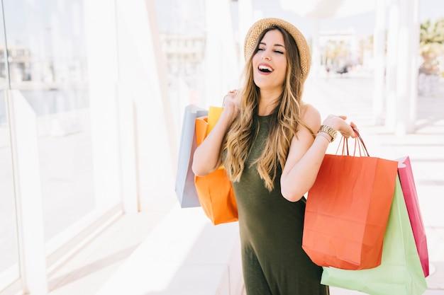 Jeune femme rire et poser avec des sacs à provisions