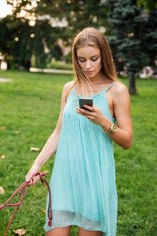 Jeune femme en robe à l'aide de téléphone portable tout en promenant son chien dans le parc